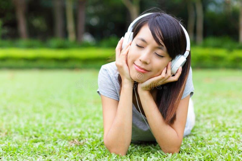 Den asiatiska kvinnan lyssnar till sången som ligger på gräs fotografering för bildbyråer