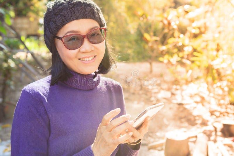 Den asiatiska kvinnan med att le framsidalyckasinnesrörelse och ilar telefonen arkivbild