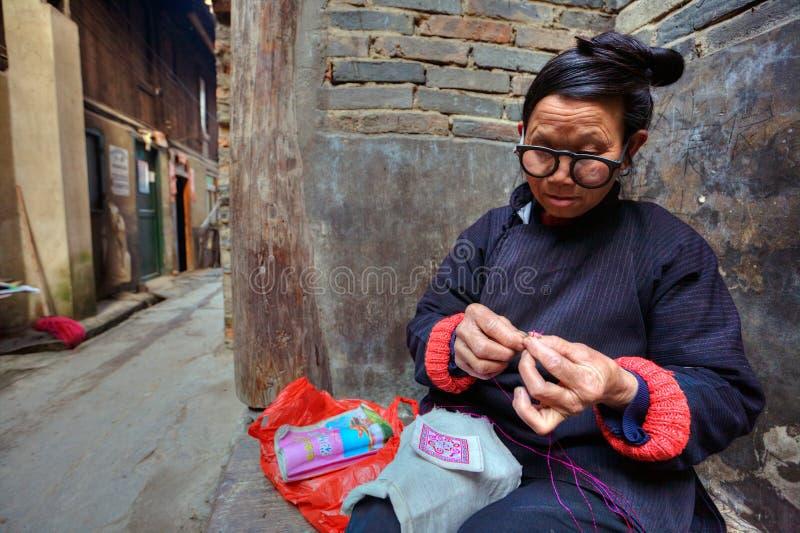 Den asiatiska kvinnan med exponeringsglas är förlovad i handarbete utomhus, hakan royaltyfri fotografi