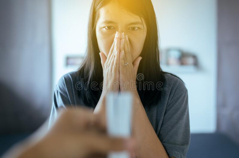 Den asiatiska kvinnan med händer täcker hennes dåliga lukt för näskänsla till den suddiga cigaretten, det inget begreppet - arkivfoton