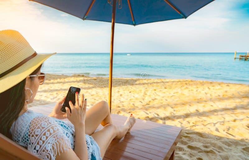 Den asiatiska kvinnan med hatten sitter på sunbed under strandparaplyet på sandstranden och användasmartphonen på sommarsemester  arkivfoton