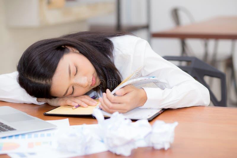 Den asiatiska kvinnan med trött överansträngt och sömn, flicka har att vila medan arbetshandstilanmärkningen royaltyfria bilder