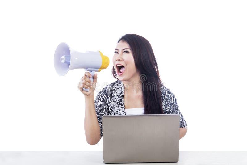 Den asiatiska kvinnan meddelar genom att använda högtalaren och bärbar dator arkivfoto