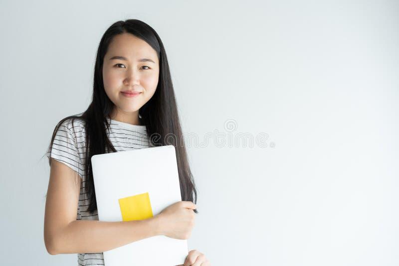 Den asiatiska kvinnan rymmer bärbara datorn på vit bakgrund, stående en så gullig ung flicka, när han ler och lyckligt royaltyfri fotografi