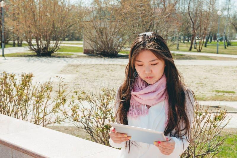 Den asiatiska kvinnan som använder den digitala minnestavlan parkerar in royaltyfri fotografi