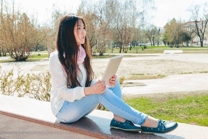 Den asiatiska kvinnan som använder den digitala minnestavlan parkerar in fotografering för bildbyråer