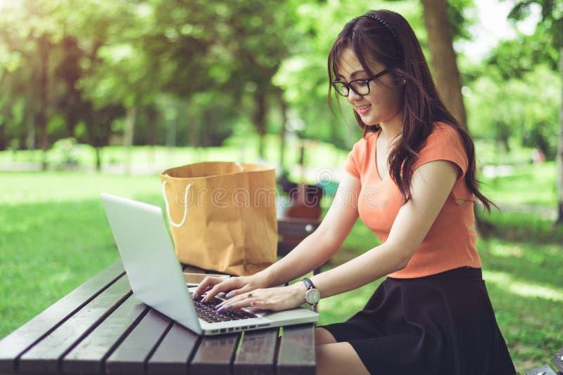 Den asiatiska kvinnan som anv?nder och skriver p? b?rbar datortangentbordet i det fria, parkerar Kvinna som pratar till hennes v? royaltyfri bild