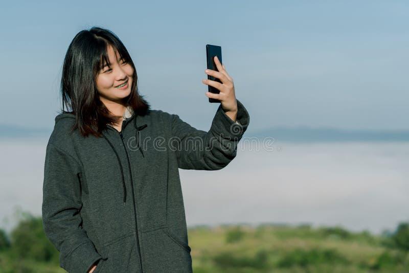 Den asiatiska kvinnan som bär ett vinteromslag, tar en selfietelefon, tar bilder i det turist- området bak dimman och bergen med  royaltyfria bilder