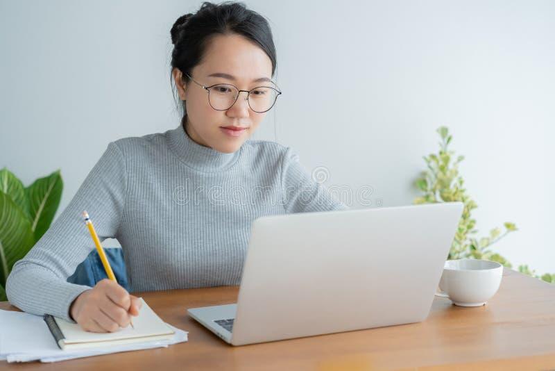Den asiatiska kvinnan som bär exponeringsglas, använder det hemmastadda kontoret för bärbara datorn Ung gullig student för ståend royaltyfri bild