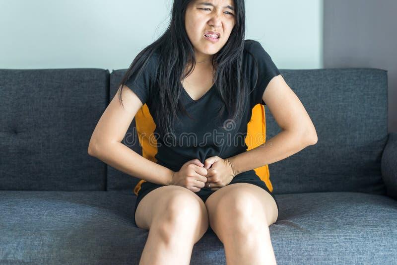 Den asiatiska kvinnan som har smärtsamt magknip på soffan efter vak upp, kvinnligt lidande från buk-, smärtar periodkramper royaltyfria foton