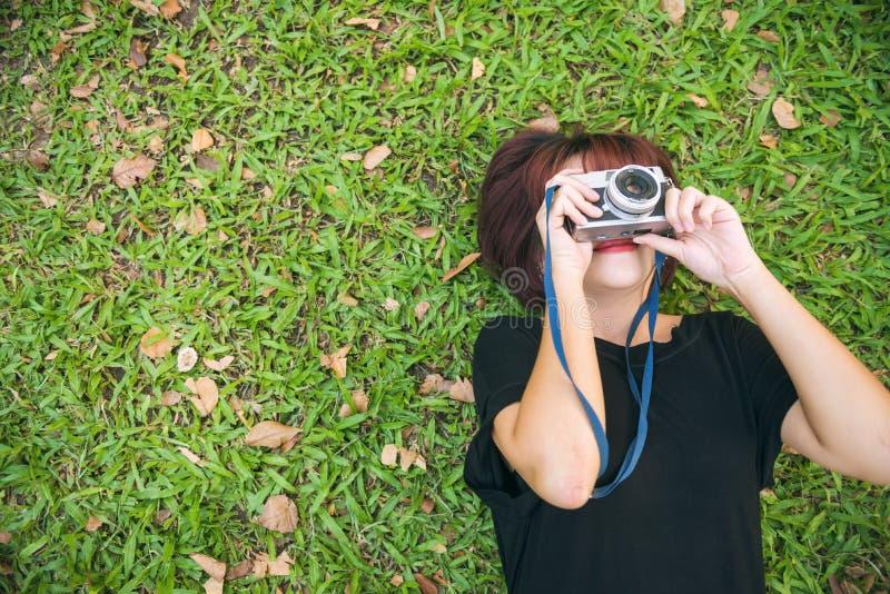 Den asiatiska kvinnan som lägger på det kyliga gröna gräset och, skjuter ett foto med hennes kamera fotografering för bildbyråer