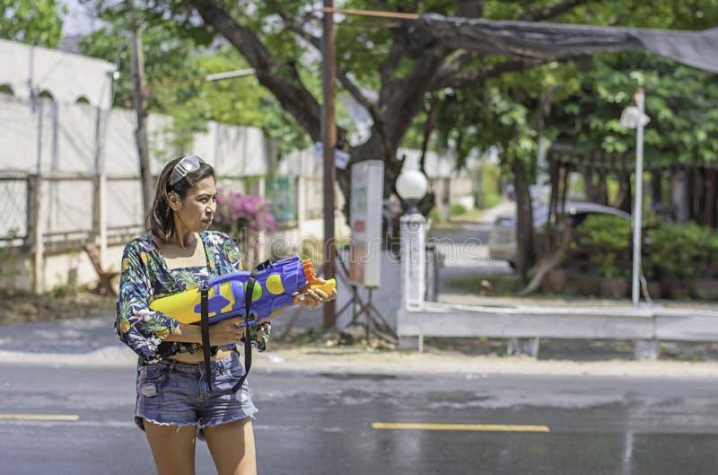 Den asiatiska kvinnan som rymmer ett vattenvapen, spelar den Songkran festivalen eller thailändskt nytt år i Thailand arkivfoton