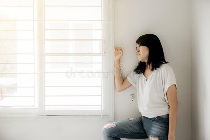 Den asiatiska kvinnan som ser något på fönster, och fördjupningen har en huvudvärk och ett frånvarande sinnat för känsla i sovrum arkivbilder