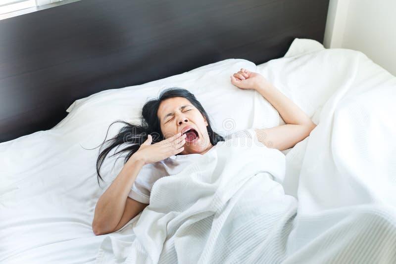 Den asiatiska kvinnan som sträcker och gäspar eller, gapar känsligt lat på säng efter vak upp i morgonen royaltyfria foton