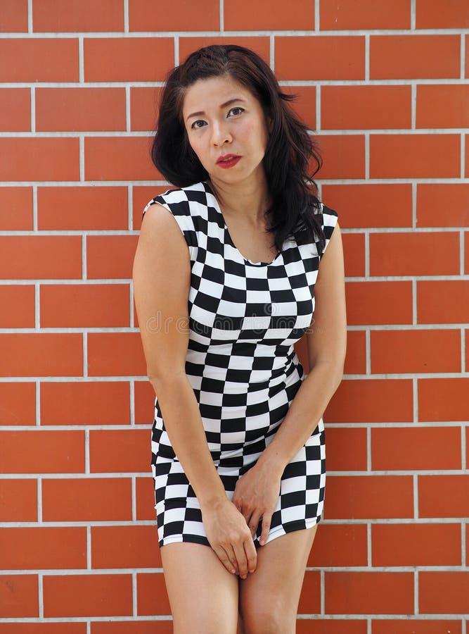 Den asiatiska kvinnan står framme av en tegelstenvägg arkivfoto