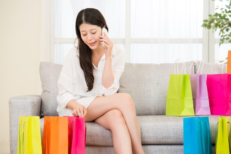 Den asiatiska kvinnan tycker om online-shopping med smartphonen arkivbilder