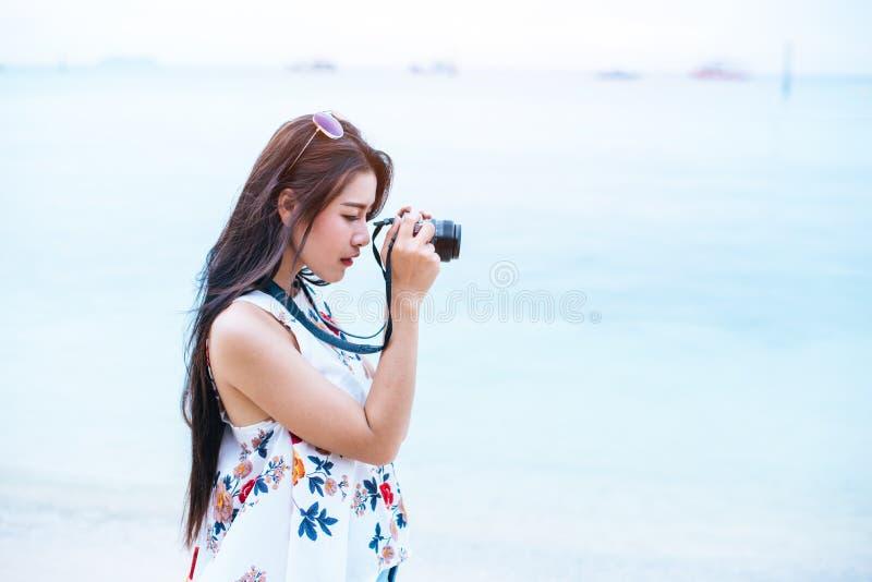Den asiatiska kvinnan tycker om tar fotoet vid den digitala kameran på stranden enkelt arkivbild
