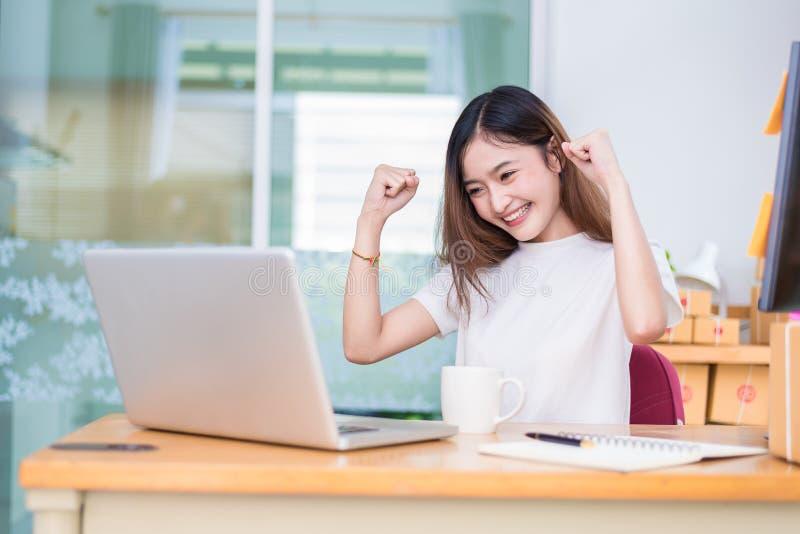 Den asiatiska kvinnan tycker sig om, medan genom att använda bärbara datorer och internet in av royaltyfri foto