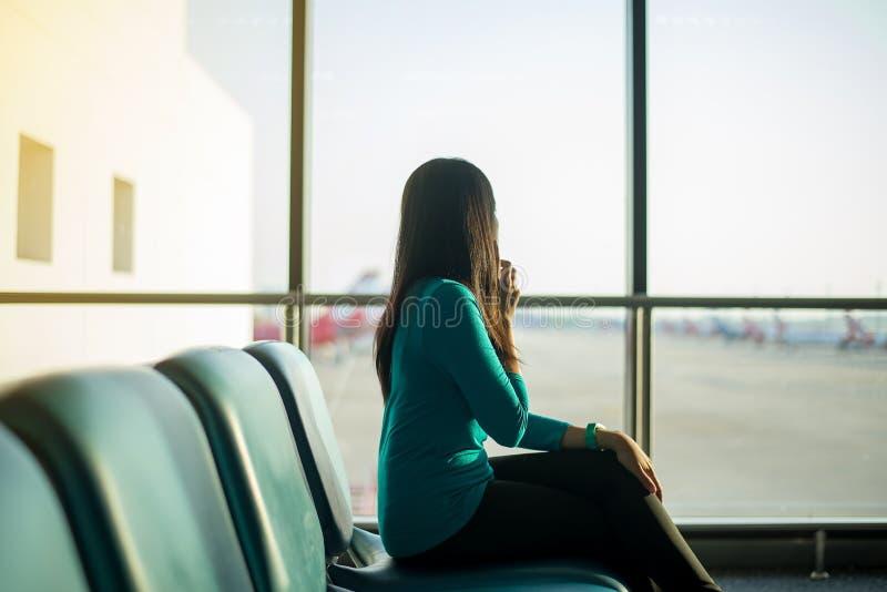 Den asiatiska kvinnapassageraren som använder smartphonen och kontrollerande flyg, eller online- kontrollerar in och reser stadsp arkivfoto
