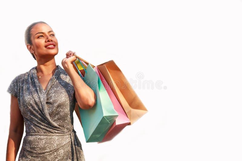 Den asiatiska kvinnashopparen är shoppa och rymma färgrika shoppingpåsar som ser sideway med kopieringsutrymme som isoleras på vi arkivfoton