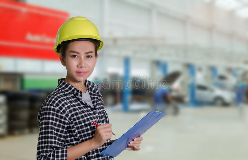 Den asiatiska kvinnatekniker- och teknikermekanikern kontrollerar, och inspectingthelistan på brädet av en bil i auto reparation  arkivbild