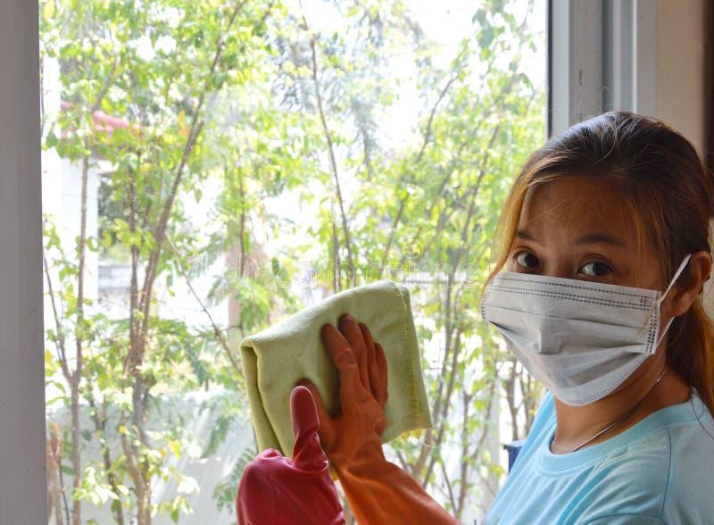 Den asiatiska kvinnawipen exponeringsglaset arbetsamt men henne bötfäller fortfarande royaltyfria foton