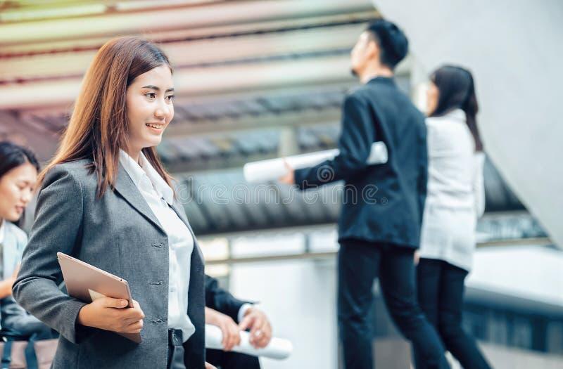 Den asiatiska kvinnliga affärskvinnan rymmer en minnestavla i affärssamröre a royaltyfria bilder