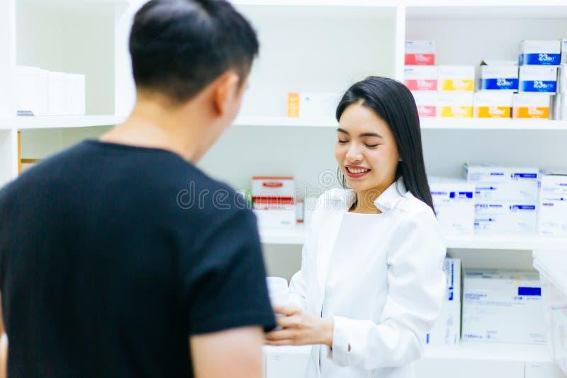 Den asiatiska kvinnliga apotekaredoktorn i yrkesmässig kappa som förklarar och ger rådgivning med den manliga klienten i apotek,  arkivbild
