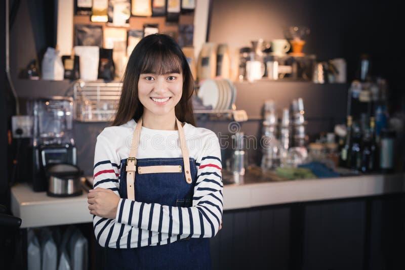 Den asiatiska kvinnliga baristaen bär blått förklädeanseende i ett kafé arkivbild