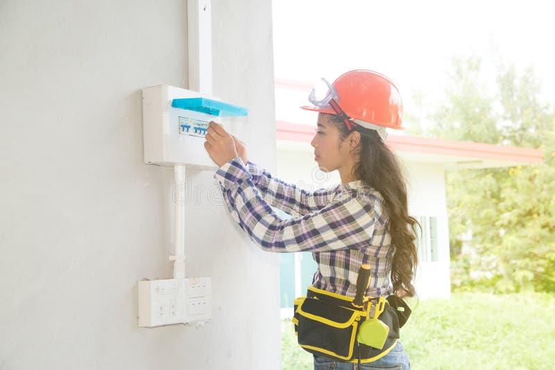 Den asiatiska kvinnliga elektriker- eller teknikerkontrollen eller kontrollerar säkerhetsbrytaren för strömkretsen för det elektr royaltyfri bild