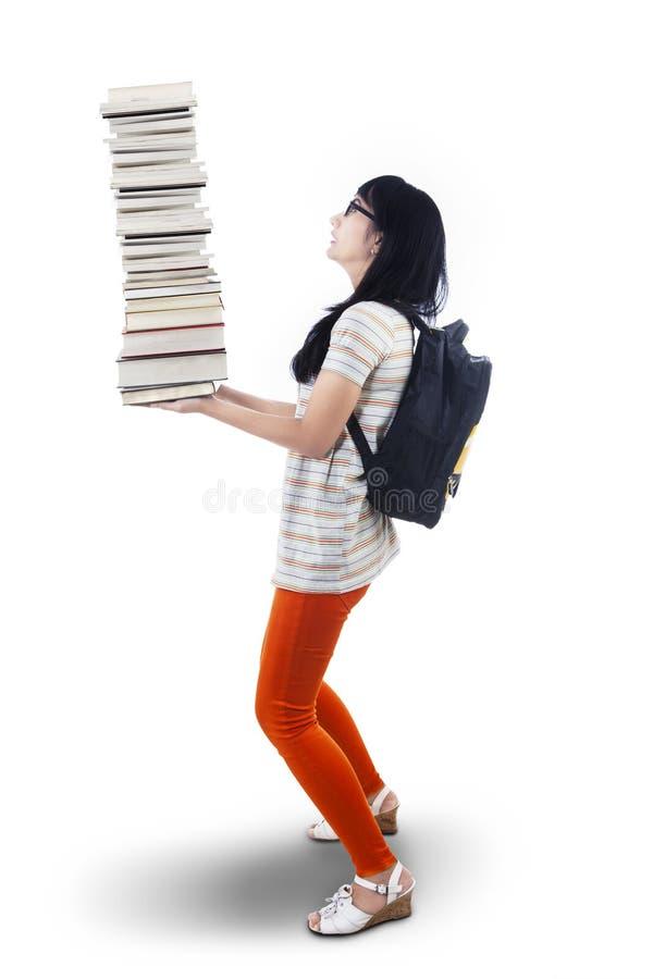 Den asiatiska kvinnliga studenten kommer med högen av isolerade böcker - arkivbild