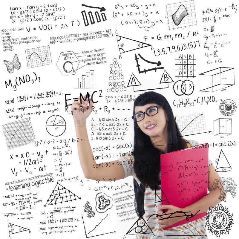 Den asiatiska kvinnliga studenten skriver på whiteboard arkivbilder