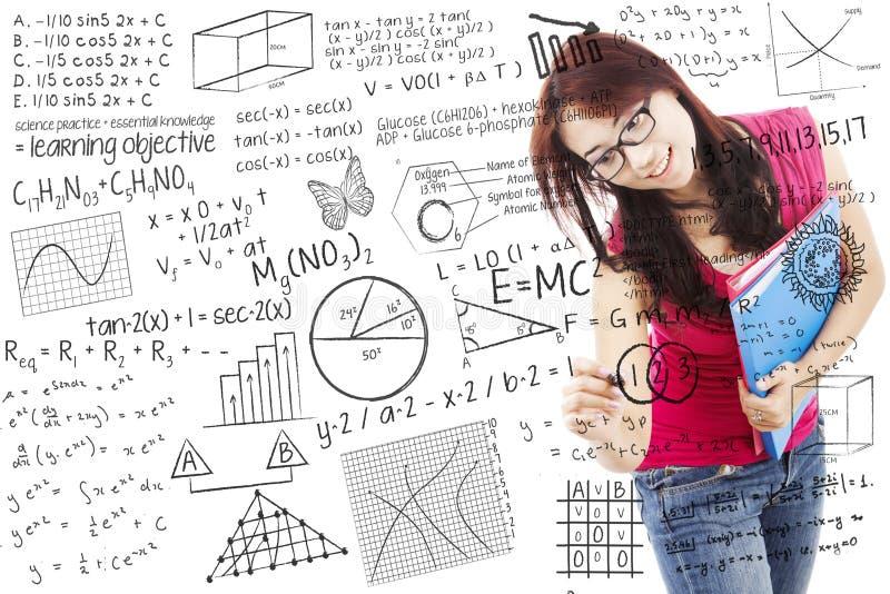 Den asiatiska kvinnliga studenten skriver på whiteboard royaltyfri foto