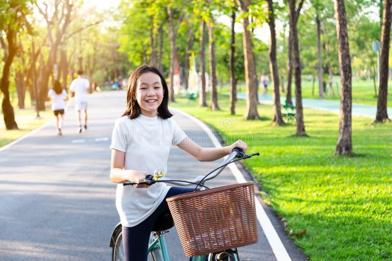 Den asiatiska lilla flickan är le, och se kameran på cykeln i utomhus- parkera, ståenden av det lyckliga gulliga barnet med cykel arkivfoton