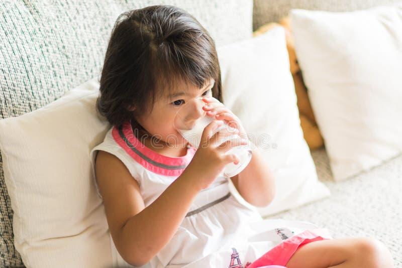 Den asiatiska lilla flickan dricker en mjölka från exponeringsglas i vardagsrum arkivbild