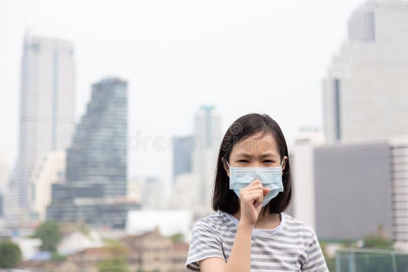 Den asiatiska lilla flickan lider från hosta med skydd för framsidamaskeringen, bärande framsidamaskering för gulligt barn på gru royaltyfria bilder