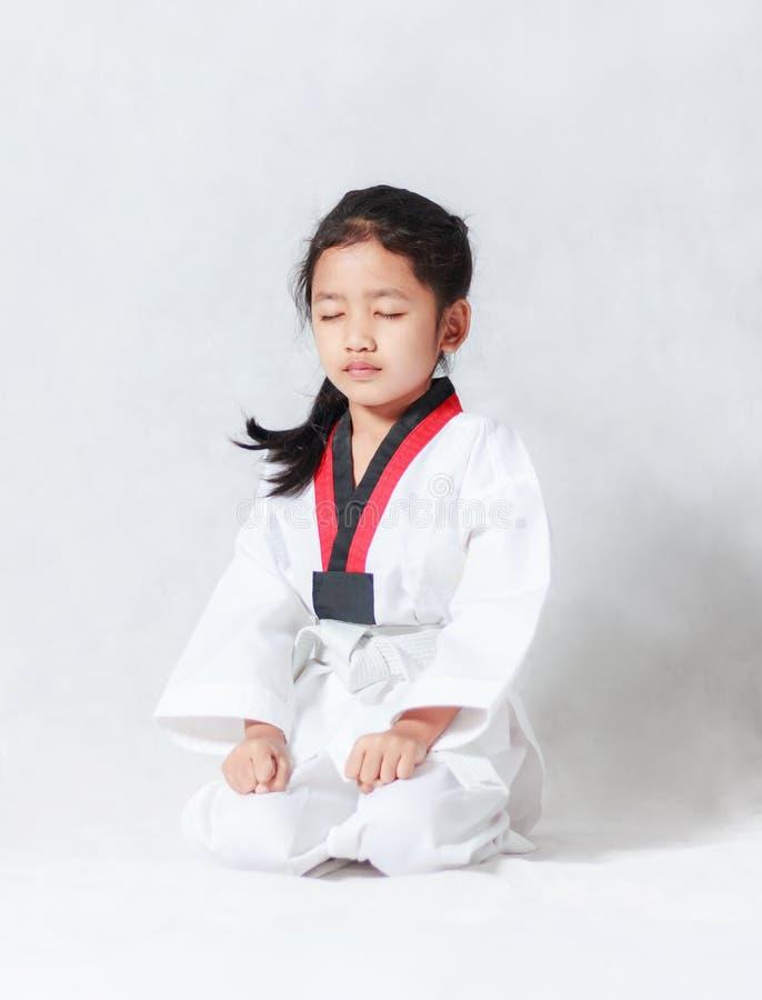 Den asiatiska lilla flickan sitter för koncentration i Taekwondo unif royaltyfria bilder