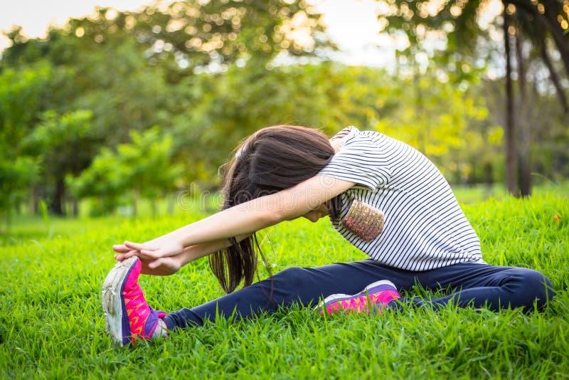 Den asiatiska lilla flickan som övar på det utomhus-, parkerar på gräsmattan är en meditationövning, barnövning i natur i morgone arkivbild