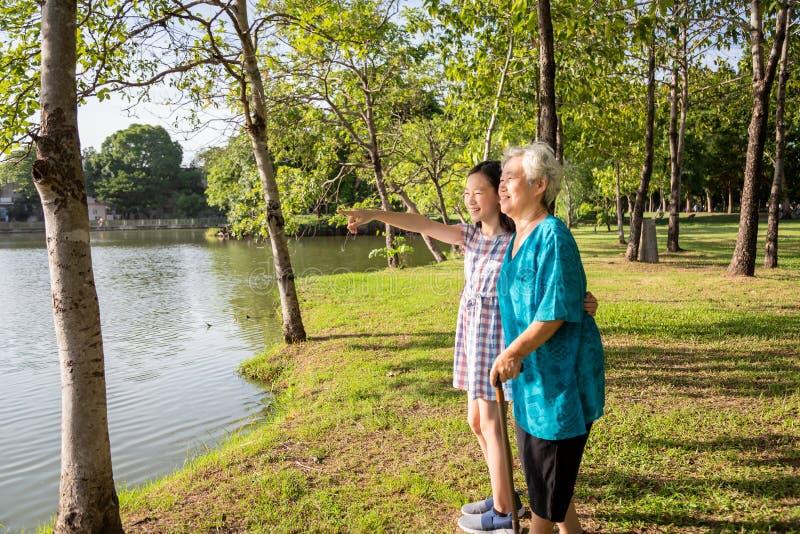 Den asiatiska lilla flickan som stöttar den höga kvinnan med den gå pinnen, den lyckliga le farmodern och sondottern i utomhus- p arkivbild