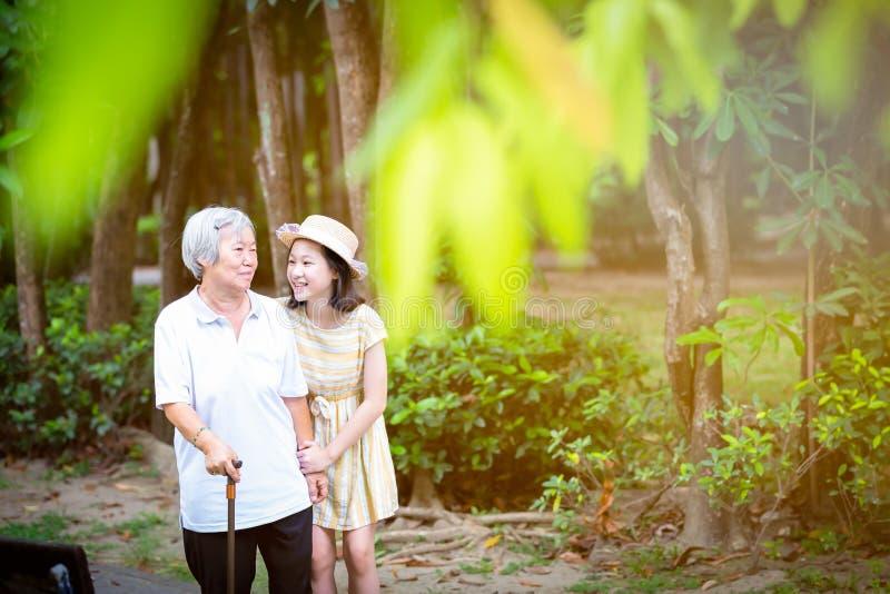Den asiatiska lilla flickan som st?ttar den h?ga kvinnan med den g? pinnen, den lyckliga le farmodern och sondottern i parkerar,  arkivfoto
