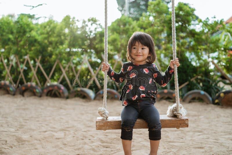 Den asiatiska lilla flickan som tycker om spela en gunga bara på, parkerar arkivbild