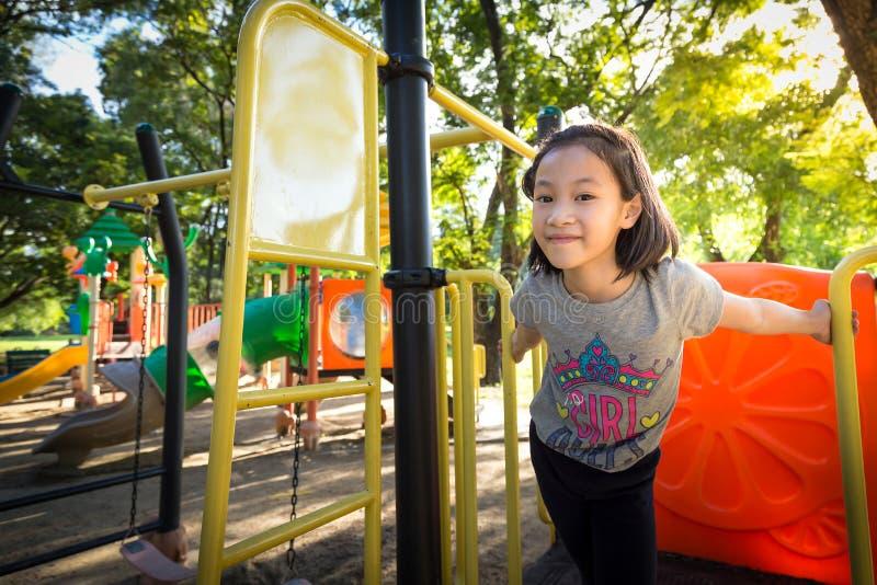Den asiatiska lilla flickan spelar på en utomhus- lekplats, och se kameran i parkera, sommar, semesterbegrepp royaltyfria foton