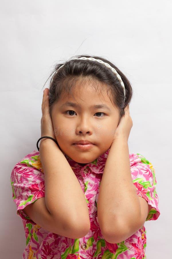 Den asiatiska lilla flickan stängde öron för att blockera ljudet arkivfoto