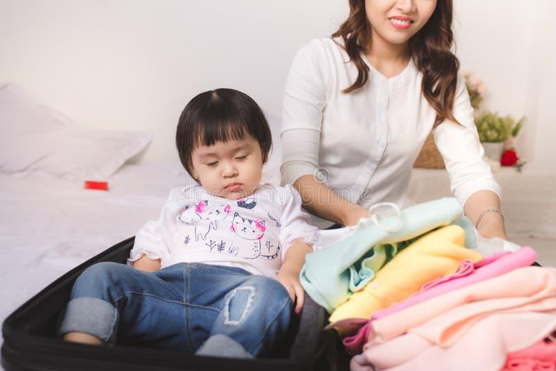 Den asiatiska mamman och behandla som ett barn flickan med resväskabagage och klar kläder arkivbild