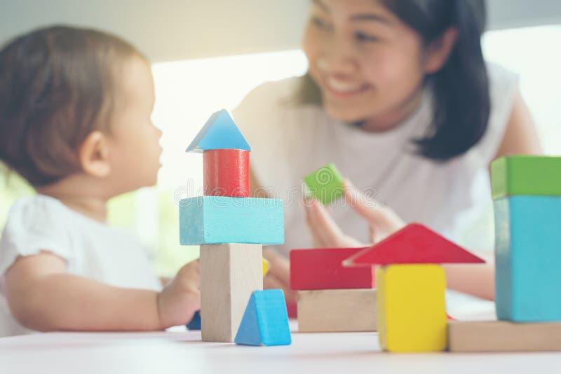 Den asiatiska mamman och flickan lurar att spela med kvarter Selektiv fokus och royaltyfria bilder