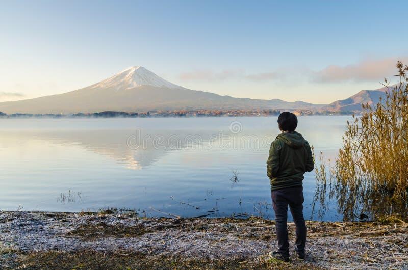 Den asiatiska manhandelsresanden som ser soluppgång, och Mount Fuji reflekterar på vatten royaltyfri fotografi