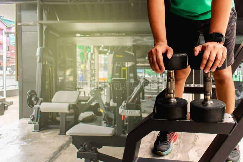 Den asiatiska mankroppsbyggaren med hantelvikter driver stiliga idrotts- övningar Metaforkondition och hälsa för genomkörarebegre arkivbilder