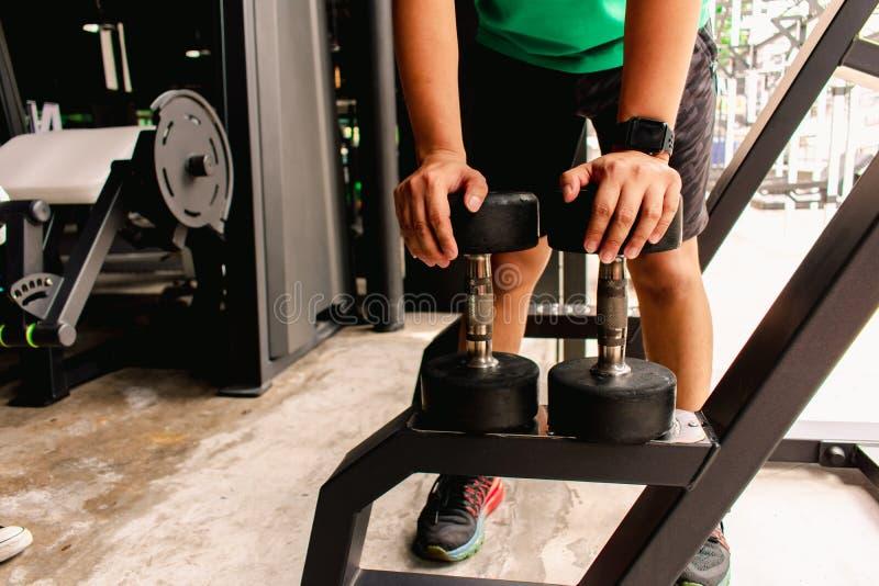 Den asiatiska mankroppsbyggaren med hantelvikter driver stiliga idrotts- övningar Metaforkondition och hälsa för genomkörarebegre royaltyfria foton