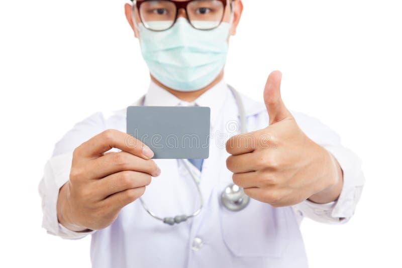 Den asiatiska manliga doktorsklädermaskeringen tummar upp med det tomma kortet royaltyfri foto