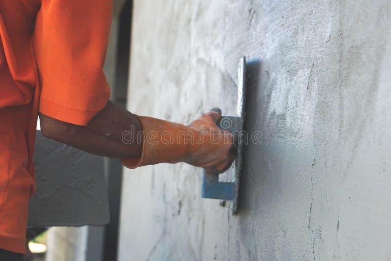 Den asiatiska manliga hus-byggmästaren handen som bär den orange handsken som slätar morteln, applicerade på en utomhus- vägg royaltyfria bilder